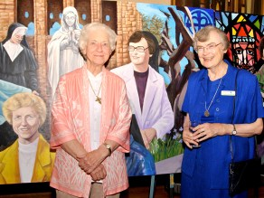 SIsters stand infront of their depictions on anniversary mural