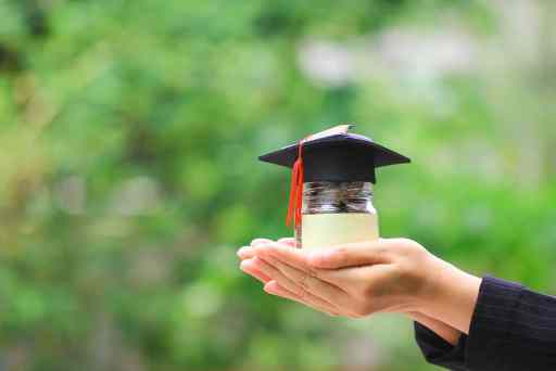 Woman hand holding coins money in glass bottle with graduates ha