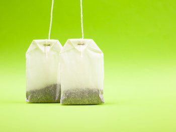 two-white-paper-bags-with-black-tea-light-green-background-copy-space-close-up