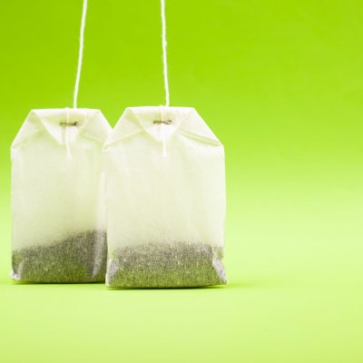 two white paper bags with black tea on a light green background copy space, close-up