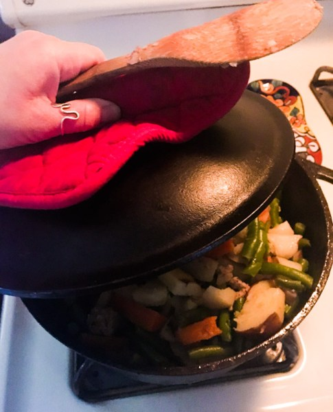 Cast iron dutch oven with meat potatoes green beans and carrots by the frugal hippie cheap easy meals
