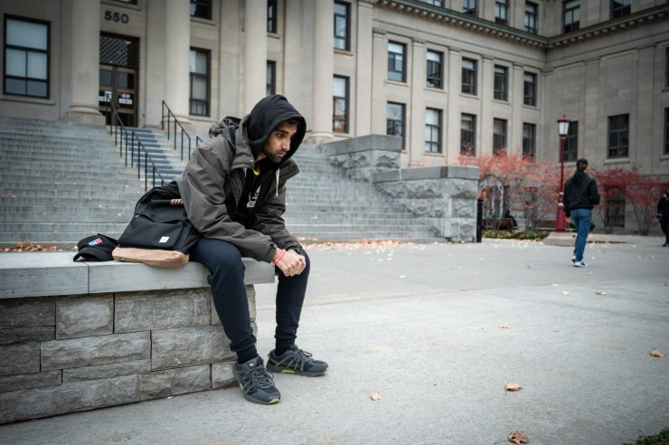 Image of a student looking sad on campus