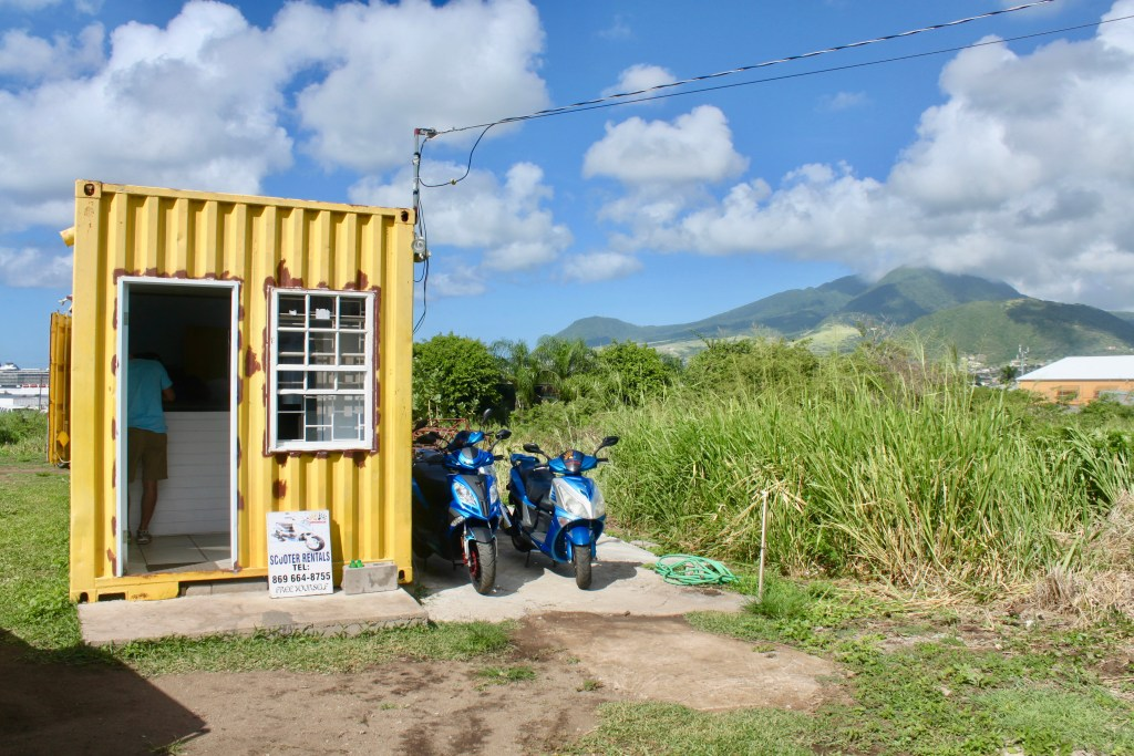 Bright yellow shipping container with a door and window and scooters parked outside. The location of our scooter rental for our St. Kitts excursion!