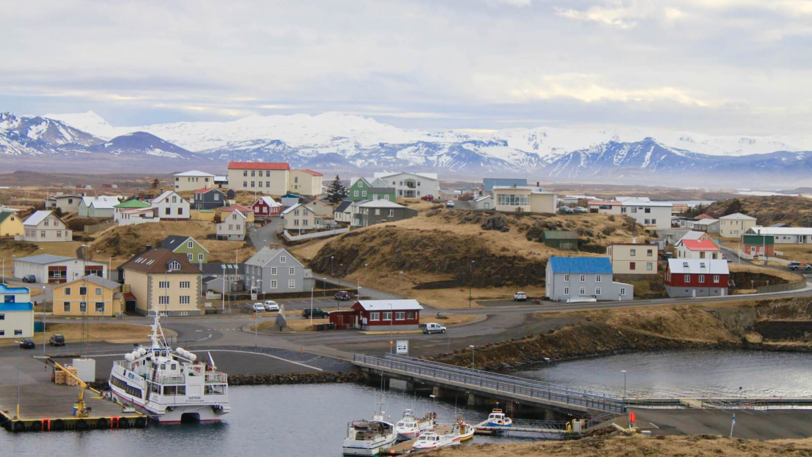 Colorful houses of Stykkishólmur dotting the harbor with mountains beyond