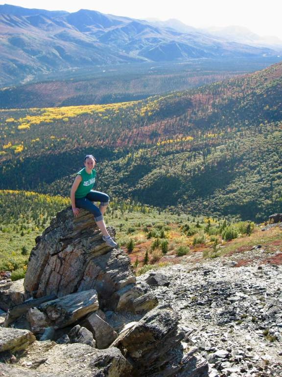 Gwen sitting on a large rock in front of a colorful valley