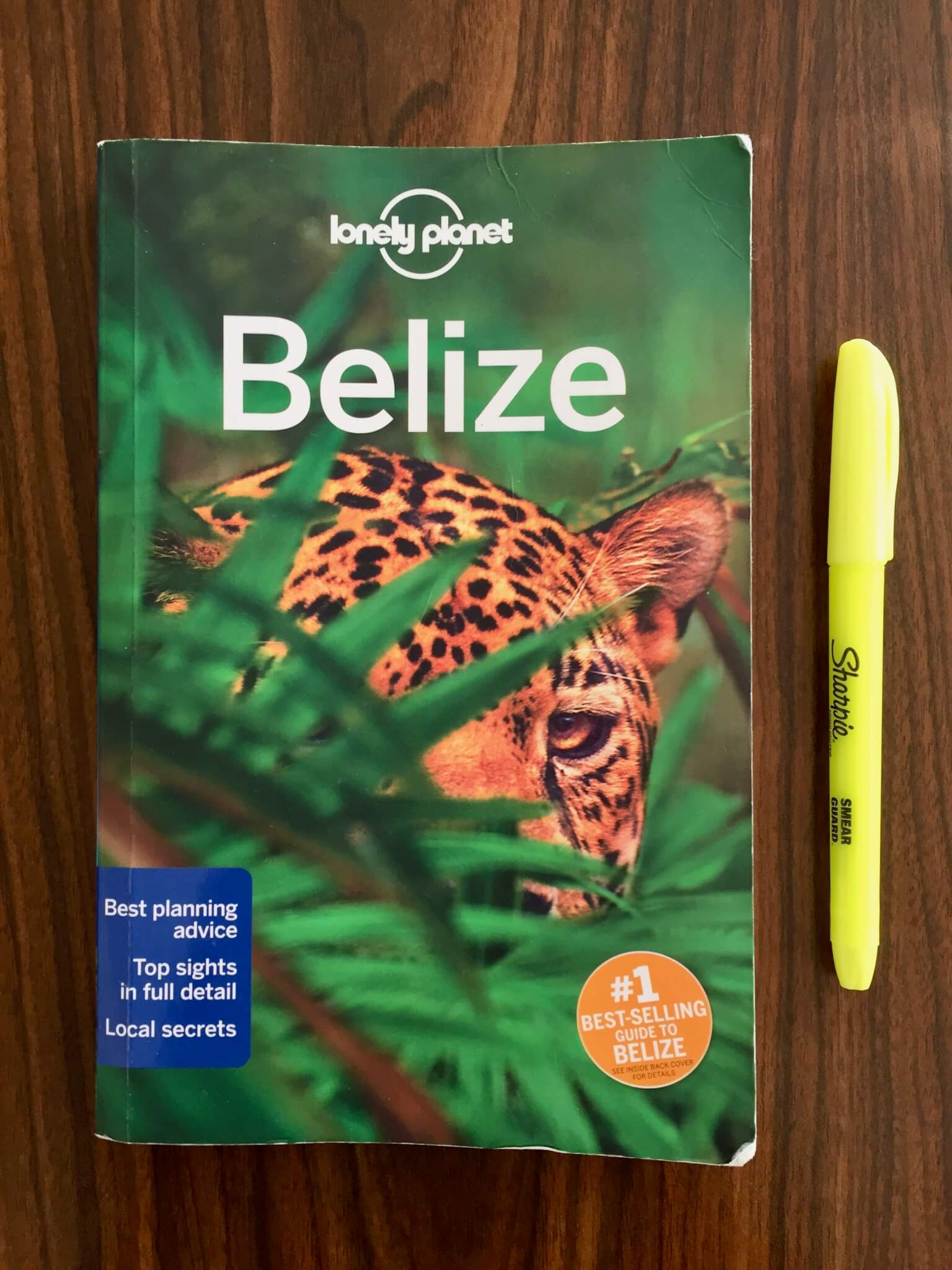Belize Lonely Planet guidebook on a wooden table with yellow highlighter
