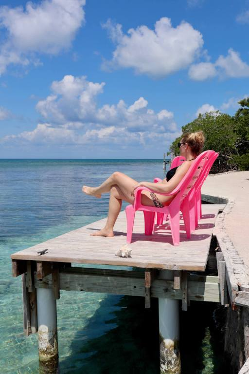 Brooke on a pink chair near the ocean on Bread and Butter Caye