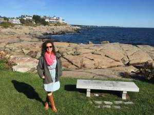 Emily in front of a rocky New England coastline