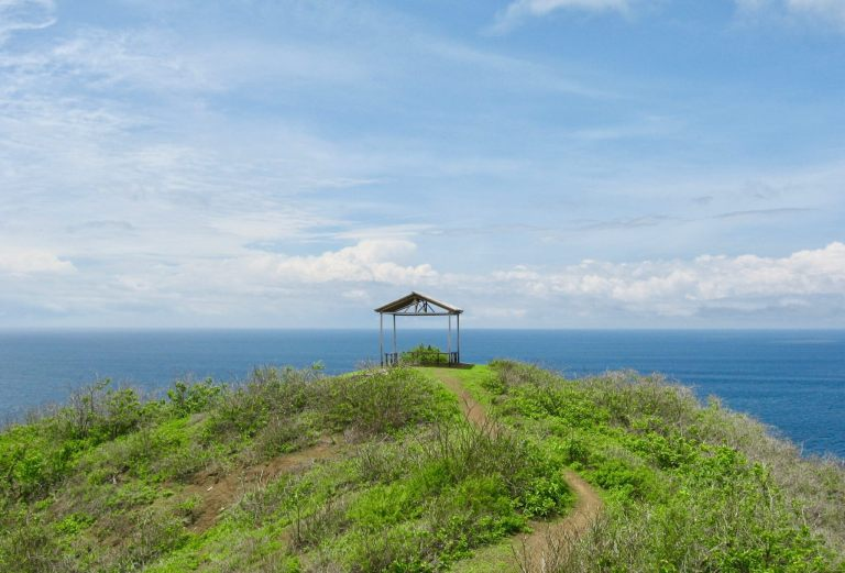Open wooden hut on a green headland with the sea beyond