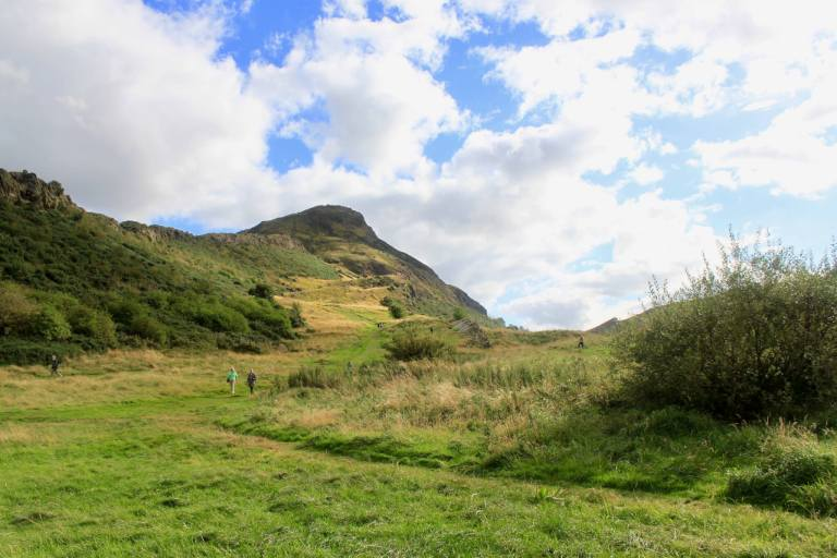 grassy parkland with Arthur's Seat in distance