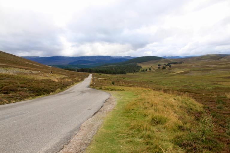 Narrow road winding through barren Highland hills. The Cairngorms are a great addition to a week in Scotland itinerary.
