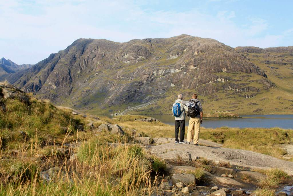 M and his dad in front of Loch Coruisk and the Cuillin Hills, a quieter spot away from the destinations on this Isle of Skye driving itinerary