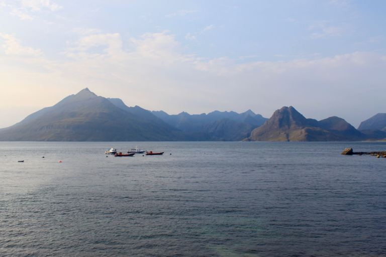 boats on the water with mountains beyond