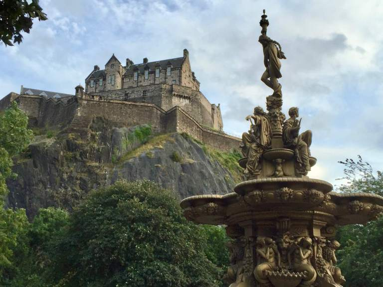 Edinburgh castle on a rocky hill behind a fountain. The castle was one of the most impressive stops on our itinerary for one week in Scotland.