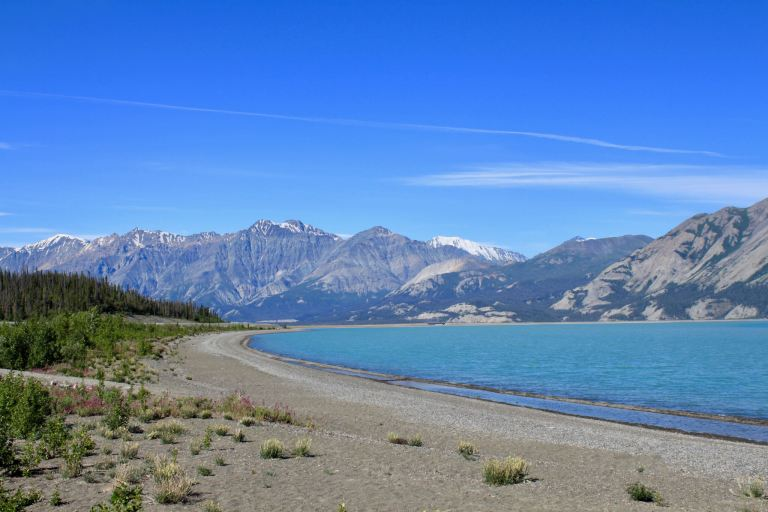 Lakeshore with bright blue water and mountains beyond. Kluane National Park is one of the best places to travel in the Yukon.