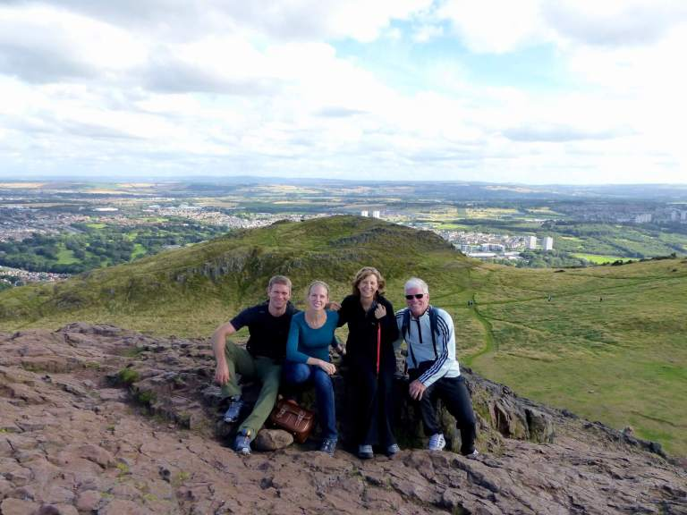 M, his parents, and Gwen atop Arthur's Seat in Edinburgh