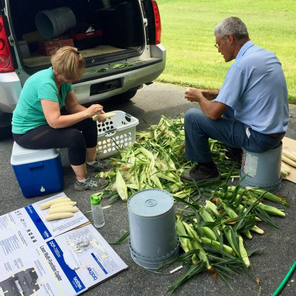 Gwen's mom and dad shucking corn
