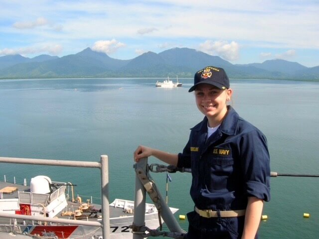 Ellen on ship with green mountains and ocean behind