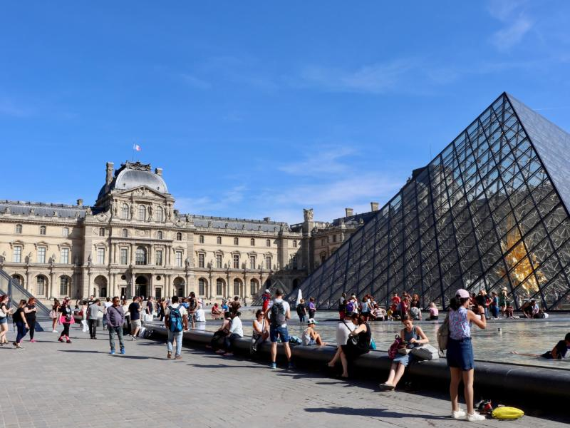 Exterior of the Louvre in Paris with glass pyramid in foreground