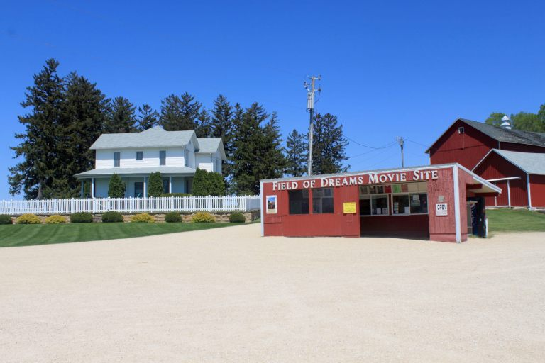 The white farm house and red barn from Field of Dreams movie with tourist shack in foreground