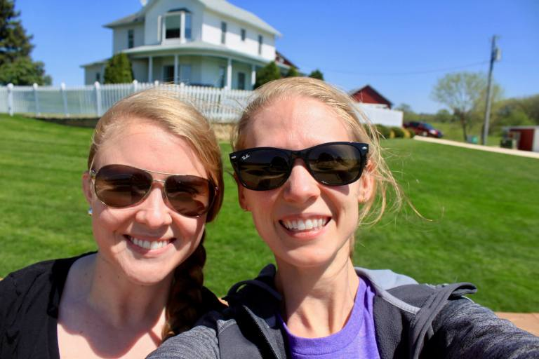 Molly and Gwen in front of the white Field of Dreams farmhouse