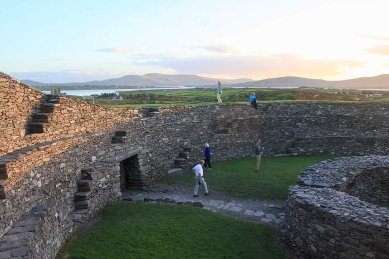 People wandering around stone structures inside ring fort