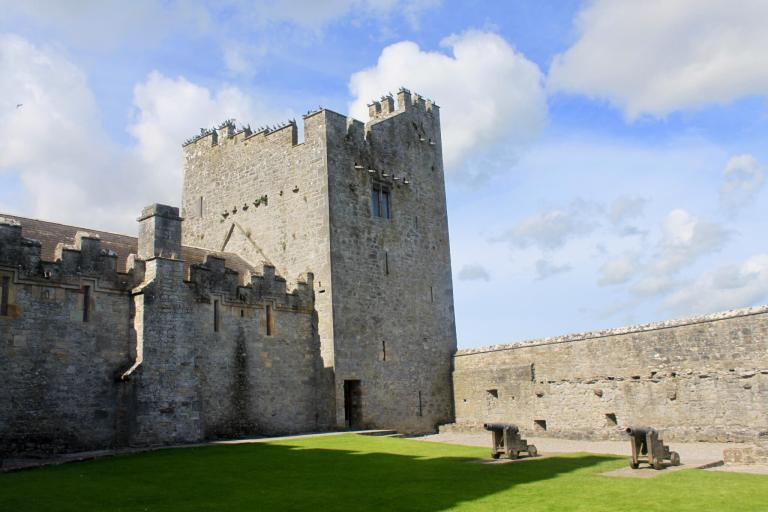 Inner courtyard of Cahir Castle, with cannons and tower.