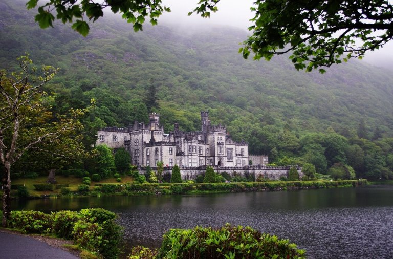 Kylemore Abbey along lake with misty forest around it