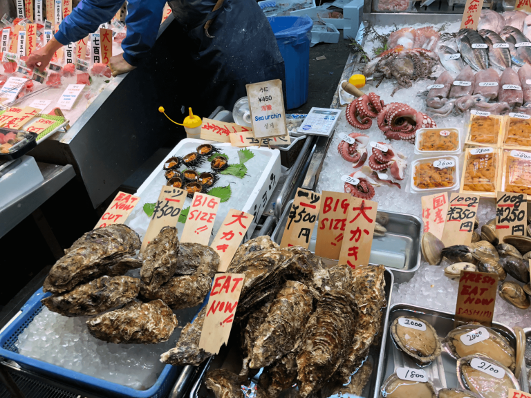 Oysters, octopus, sea urchins, and other seafood products on ice at a market
