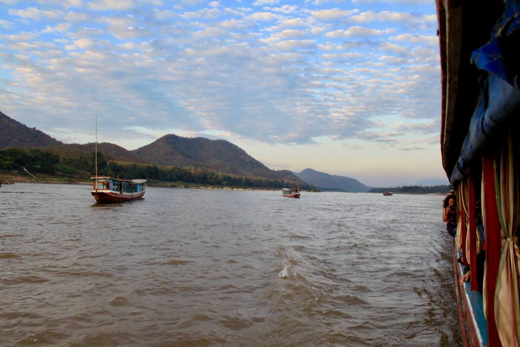 Longboats coming up behind as dusk falls and the sky is filled with color - the end of a beautiful Laos Mekong River Cruise