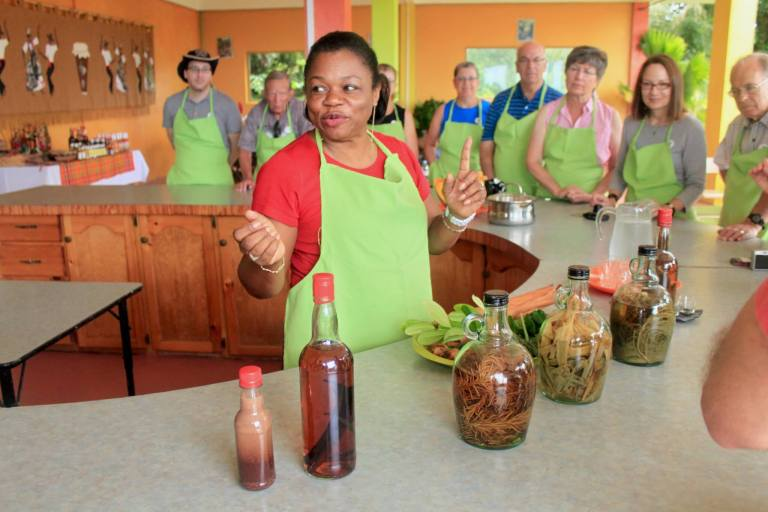 Woman in green apron describes the various rums on the table in front of her