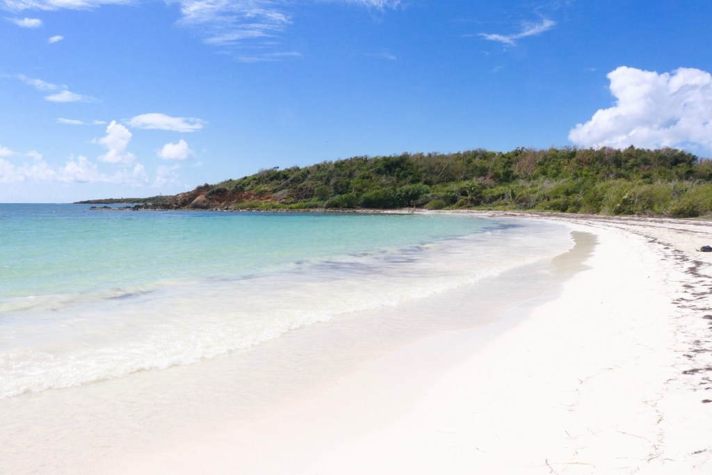 Half-moon shaped La Plata beach on Vieques with white sand and teal water