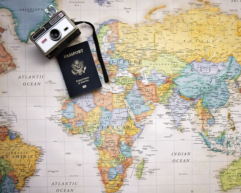 World map with passport and camera