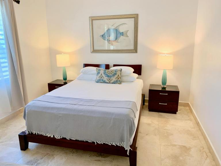 Bed at the Malecon House with pretty lamps and fish painting above