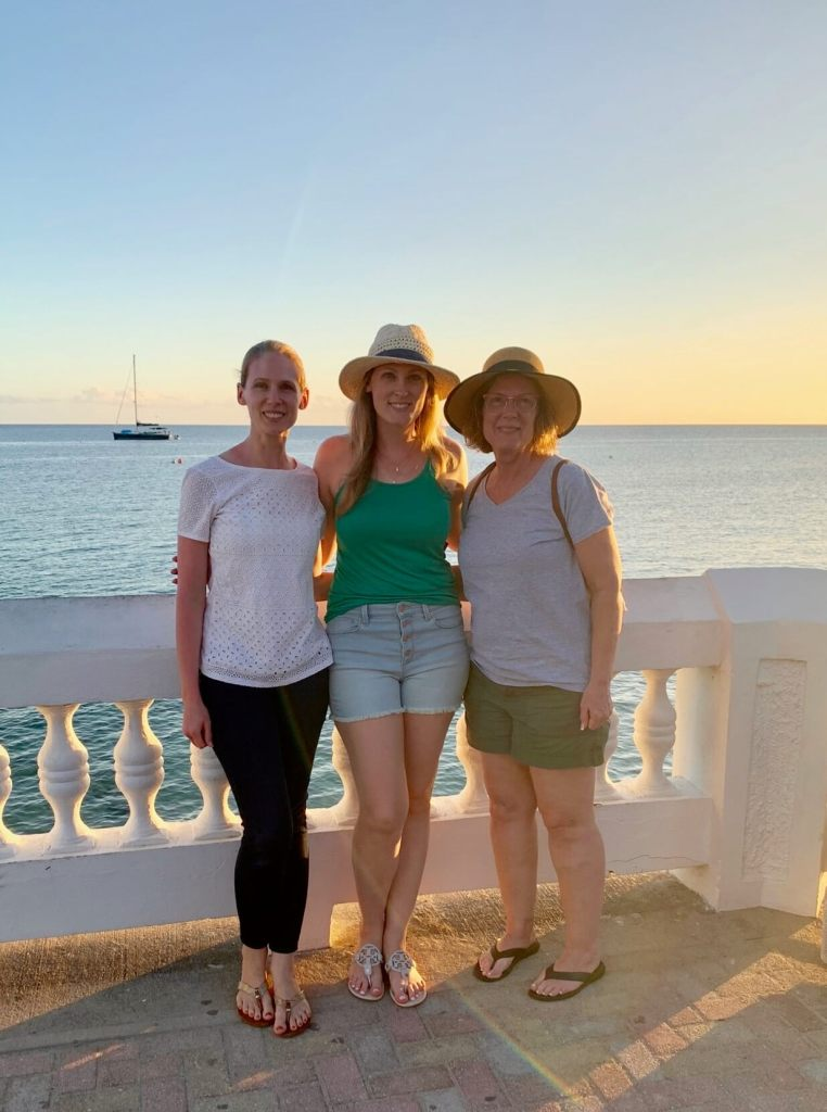 Gwen with her mom and sister in front of the ocean at sunset at our second mother-daughter trip destination: Puerto Rico