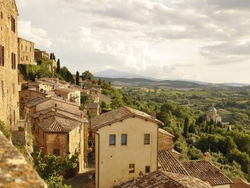 Charming old Italian village on a hillside with Tuscan countryside beyond