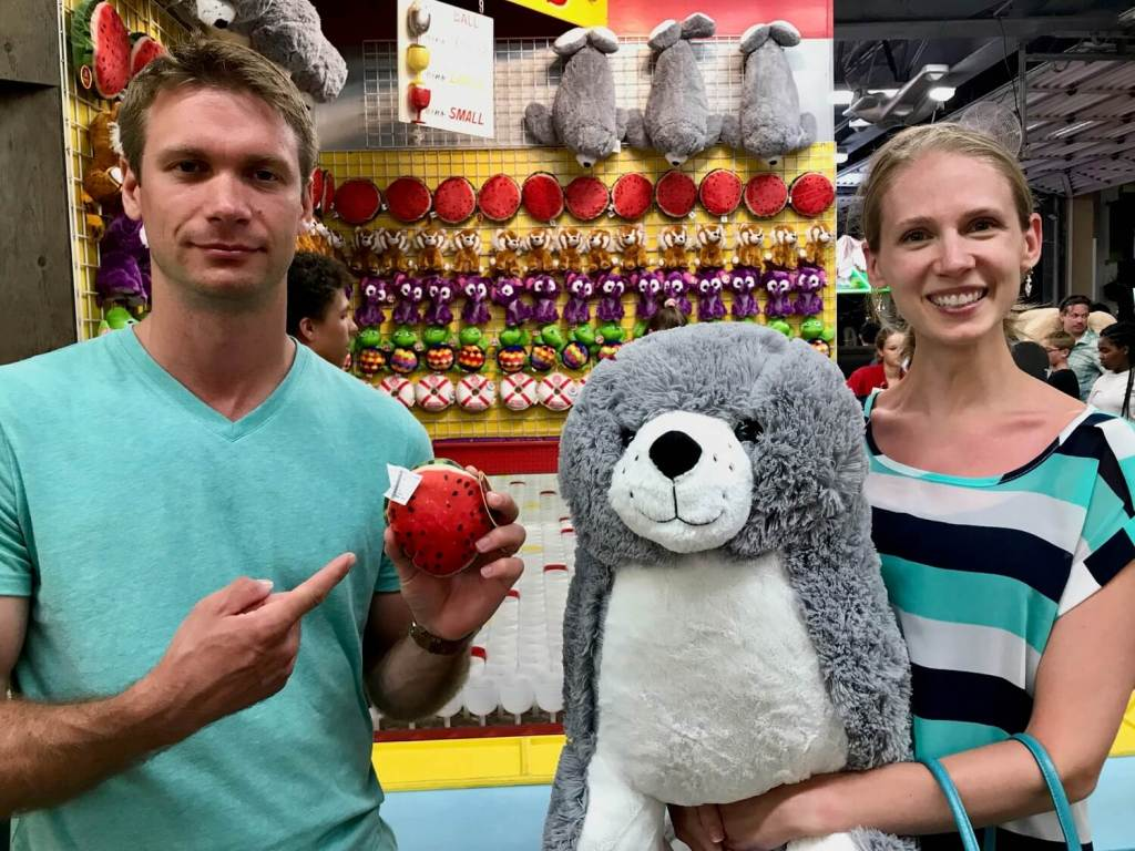 M holding a tiny watermelon stuffed animal beside Gwen, who is holding a giant stuffed seal