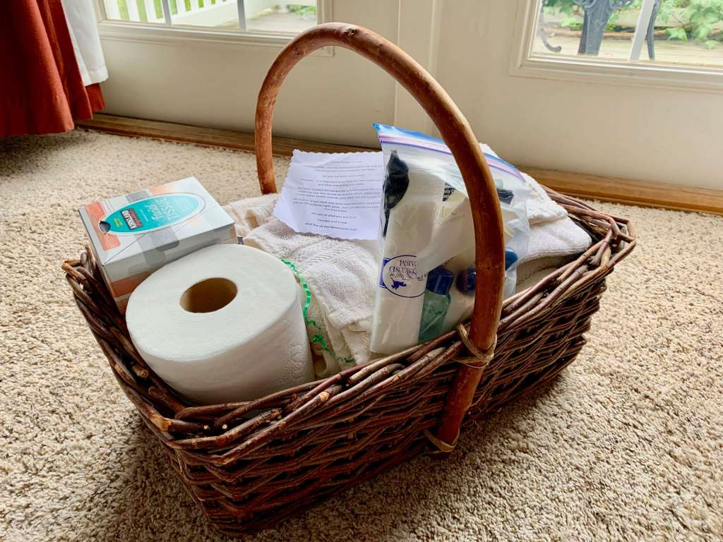 Basket of goodies, including toilet paper, tissues, towels, and toiletries