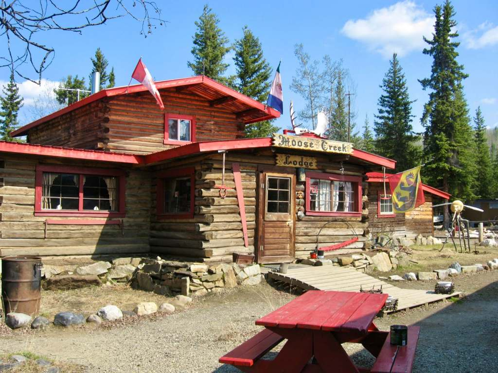 """Red-roofed log cabin with """"Moose Creek Lodge"""" sign - a worthy lunch stop on your Yukon itinerary"""