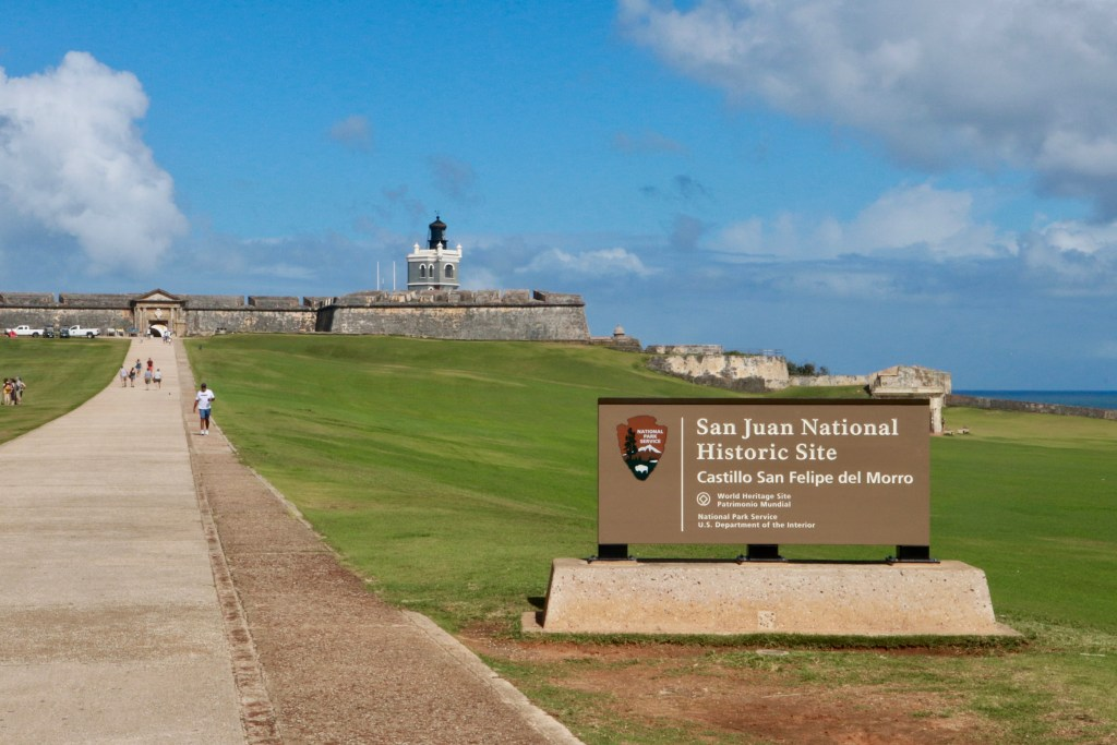 View of Castillo San Felipe del Morro park service sign with fort beyond