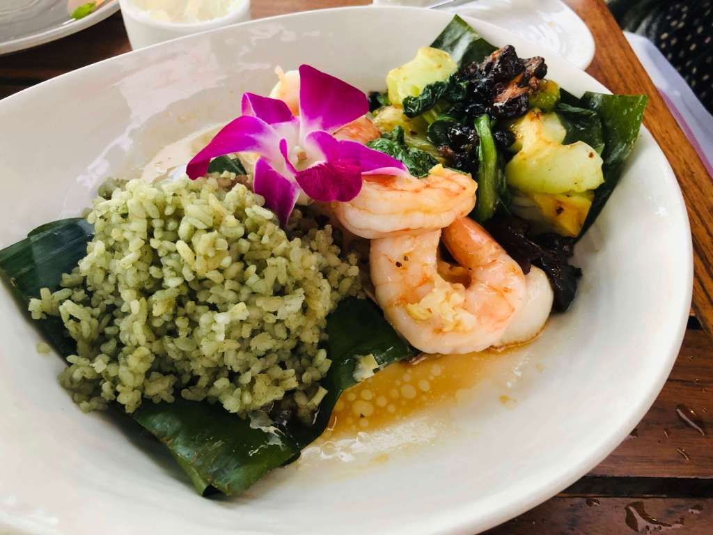 Colorful meal of rice, shrimp, pineapple, and more with a purple flower for garnish