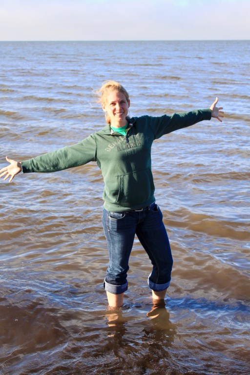 Gwen with arms spread wide ankle deep in the Arctic Ocean