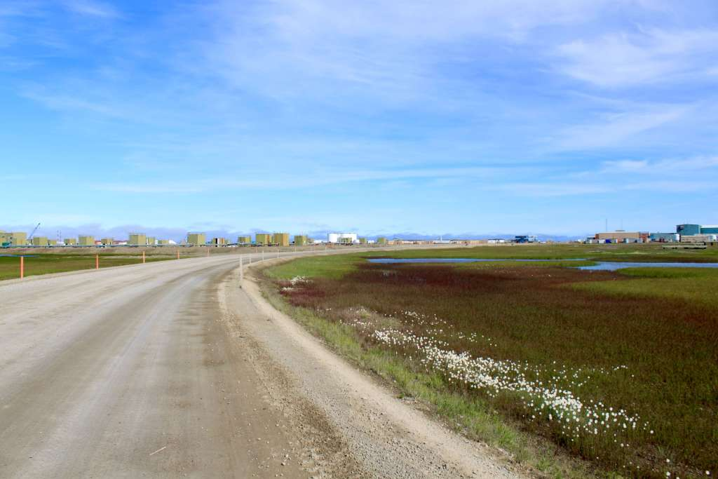 Dirt road flanked by oil buildings and storage containers in Prudhoe Bay