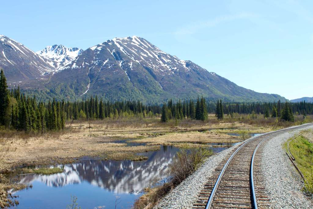 Railroad tracks cutting through forest and marshland below snow-capped mountains.