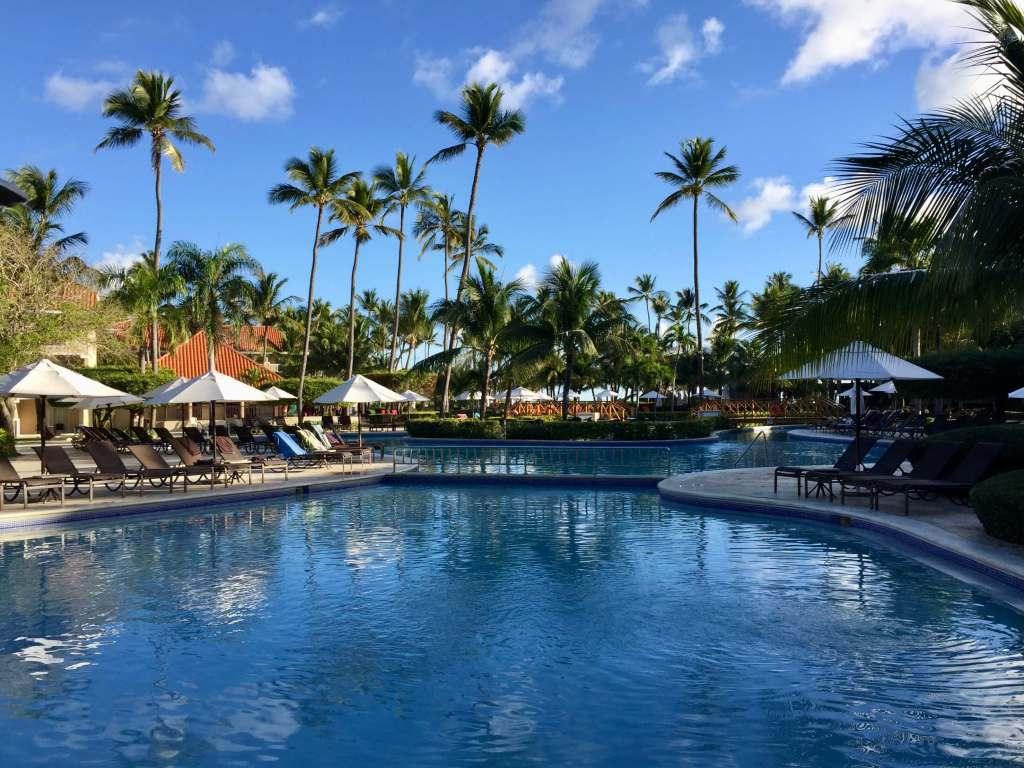 The pool area of an all-inclusive resort in the Dominican Republic, ringed by chairs, umbrellas, and palm trees.