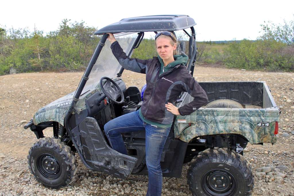Gwen making a tough face in front of an ATV.