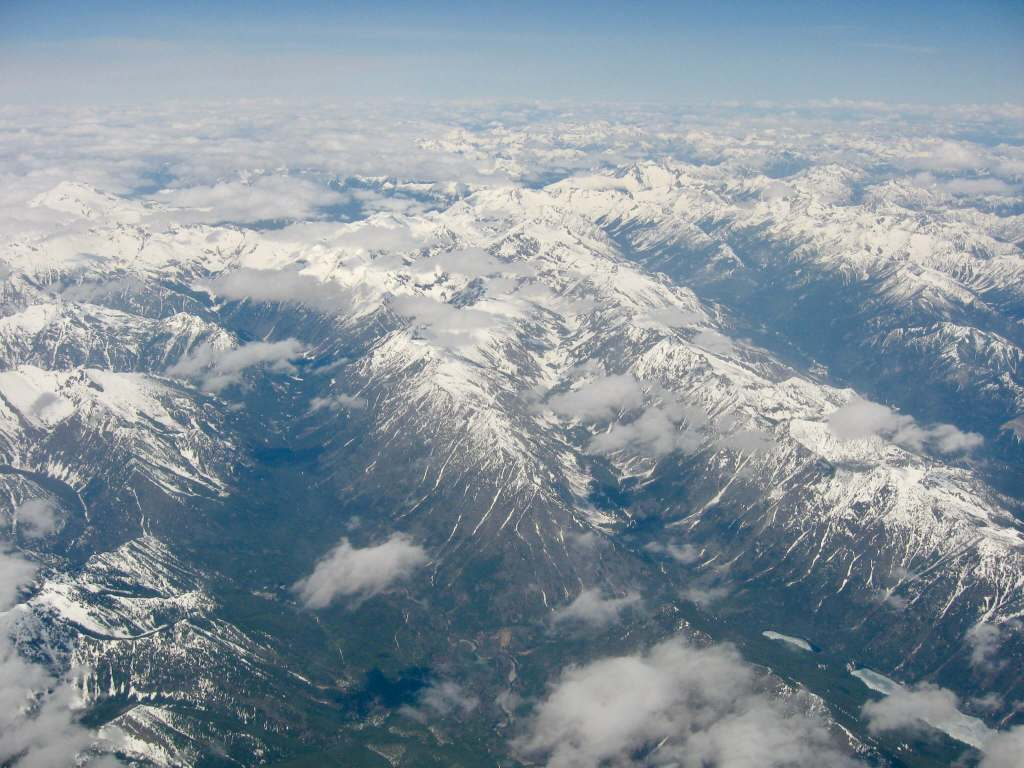 Snow-capped mountains as far as the eye can see as captured from a plane window