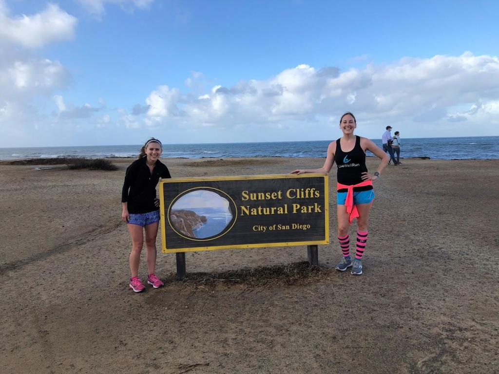 Friends posing by the Sunset Cliffs sign