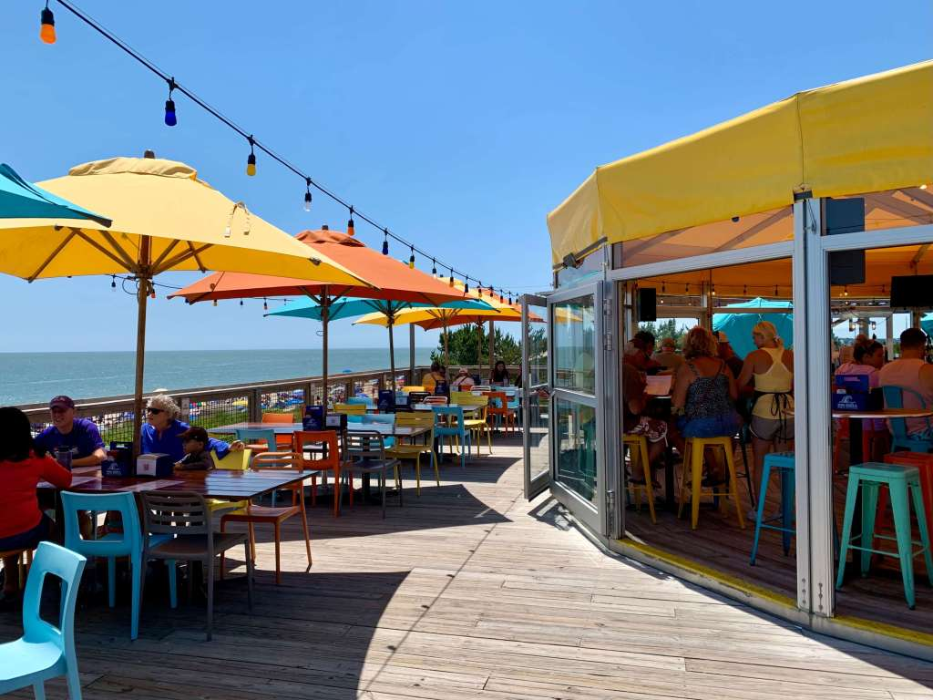 Top deck at the Big Chill Beach Club, with colorful umbrellas and chairs and ocean beyond