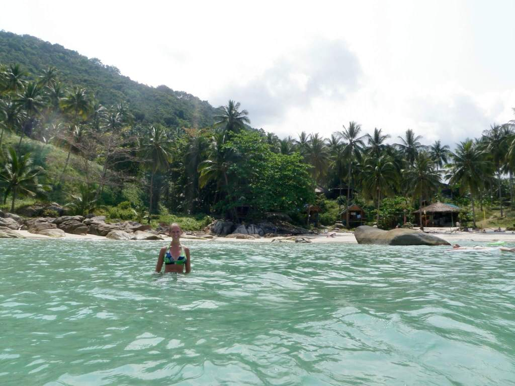 Gwen in the water with the palm tree-lined shore behind